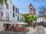 Street cafe on Rua Silva Lopes in the Old Town (Cidade Velha) with the Igreja de Santo Antonio behind, Lagos, Algarve, Portugal. CPFB1G