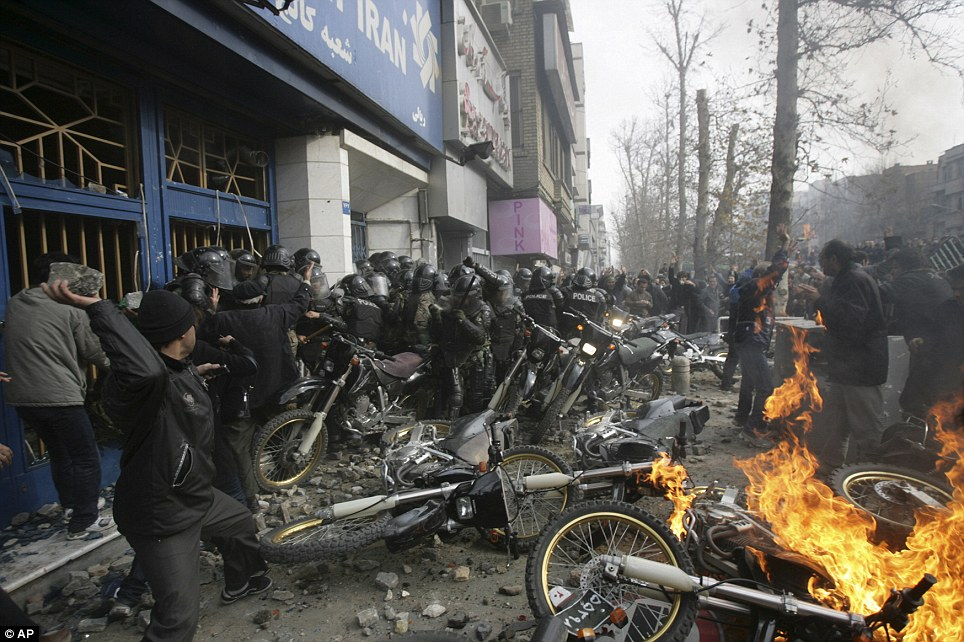 A protester, left, throwing a rock at anti-riot police officers, as their bikes are set on fire