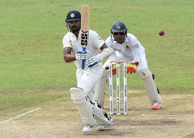 India's Murali Vijay (L) plays a shot as Sri Lanka's wicketkeeper Dinesh Chandimal looks on during the fourth day of their second Test match, at the P. Sara ...