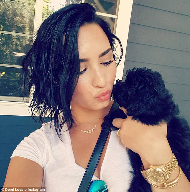 Puppy love: Demi gives a smooch to her new puppy Batman, who was a birthday gift. The singer was left devastated when her dog Buddy was attacked and killed in her backyard by coyotes last month