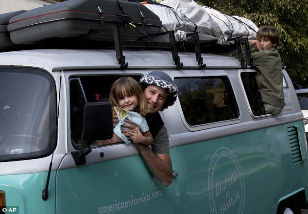 Parenthood: Catire Walker poses for a photo with his three-year-old daughter Carmin, and eight-year-old son Dimas Noel Walker, 39, while sitting inside their Volkswagen bus, in Mexico City, Saturday
