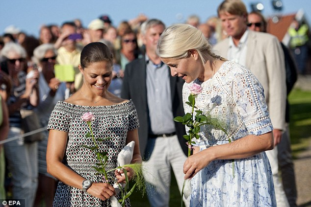 Receiving roses: The royal pair were greeted with roses as they strolled to the service and were snapped by locals