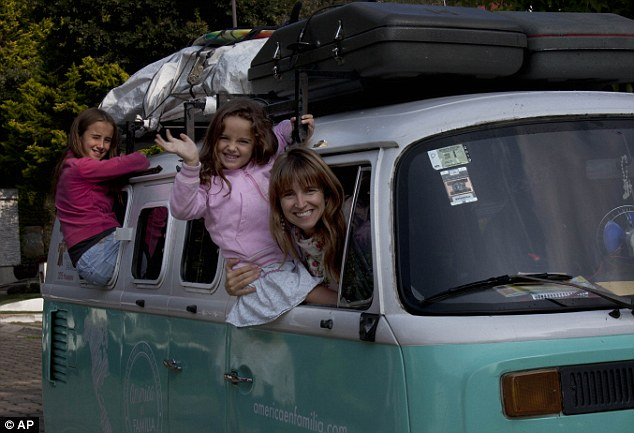 Family: Noel Walker, 39, poses for a photo with two of her children, Cala, 12, left, and Mia, 5, looking out from their Volkswagen bus, in Mexico City, Saturday