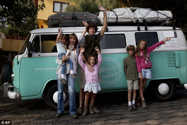 Catire Walker, 41, his wife, 39, and their four children, Carmin, 3, from left, Mia, 5, Dimas, 8, and Cala, 12, pose for a photo in front of their Volkswagen Kombi