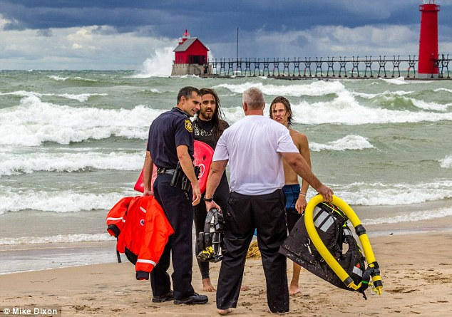 Congratulated: Boeskool said of the moment he rescued the Jozalin Francis from Grand Haven, around 15 miles from Muskegon: 'I could see her floating there and it looked like a log.' Above, the surfer and another man speak to officials later on Thursday