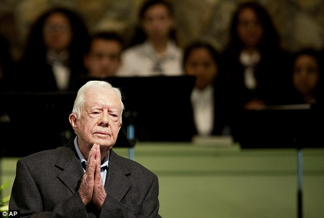Former President Jimmy Carter holds his hands in prayer as he tells his Sunday school students to recognize God in their lives
