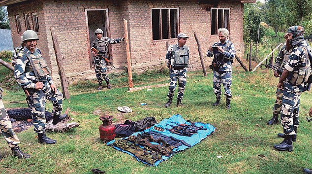 Security personnel inspect the arms and ammunition recovered from the three militants at the site of the encounter