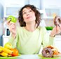 A stock photo of a beautiful Young Woman choosing between Fruits and Sweets
