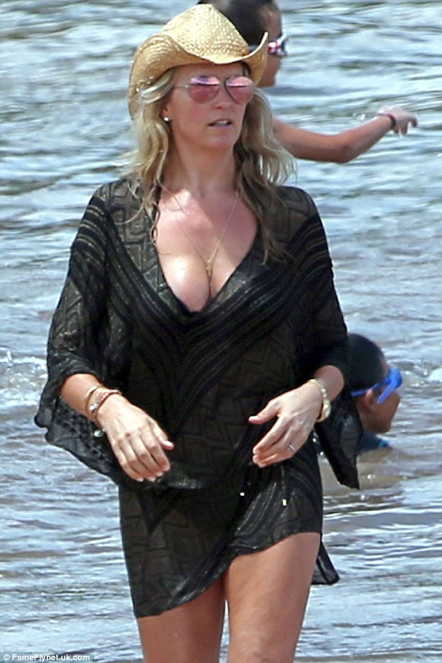 Yummy mummy: Penny looked super glamorous as she strutted through the ocean in her dainty cover-up