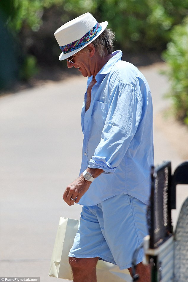 Dapper in blue: Rod Stewart looked typically cool in a pair of blue swim shorts which he dressed up with a blue shirt that was slightly unbuttoned, as he stuck to dry land