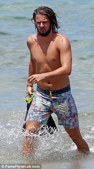Flipping heck! Liam was seen carrying his flippers as he left the ocean after a lengthy swim