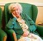 Portrait of an elderly lady aged 90 in armchair in nursing home looking very sad.  A2KTBM