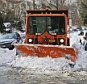 Sanitation clears a path on Grosvenor Lane Monday, Jan. 25, 2016, in the Queens borough of New York. Snow-covered cars and driveways blocked by snow from plows are causing headaches for many New Yorkers. (AP Photo/Frank Franklin II)