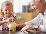 CEDHPM Caucasian grandfather watching granddaughter putting coin into piggy bank