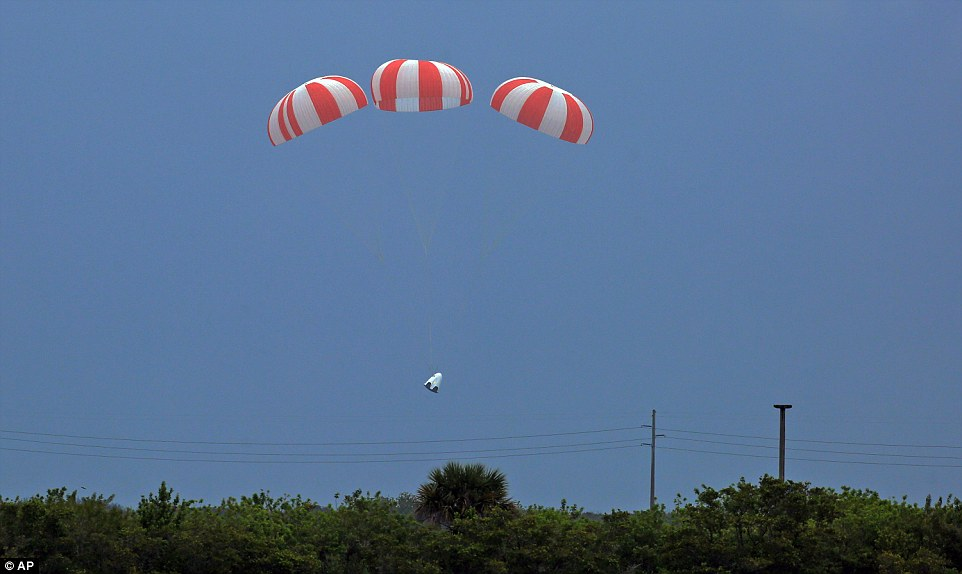 Here the spacecraft is seen with its main parachutes deployed as it descended into the ocean