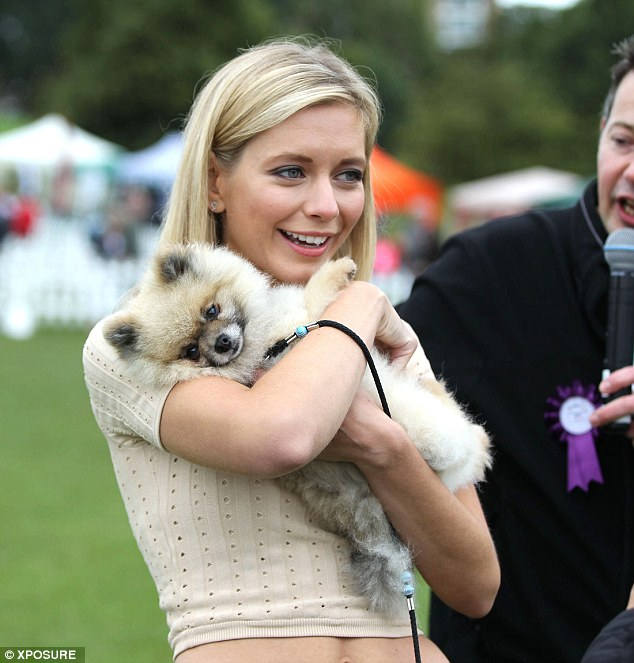 Pet lover: The pretty blonde was seen cuddling an adorable pooch on the day