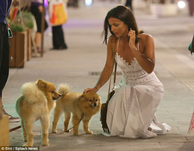 Cute! The star appeared in good spirits as she rang in the end of her short break with her sister, bending down to stroke a pair of fluffy dogs during her evening walk