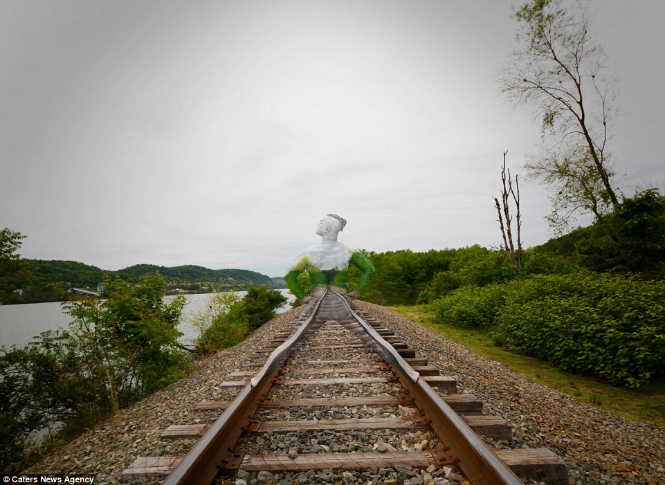 Train track: This incredible picture of a man shows him blending in with the scenery as he stands on a railway track near a river