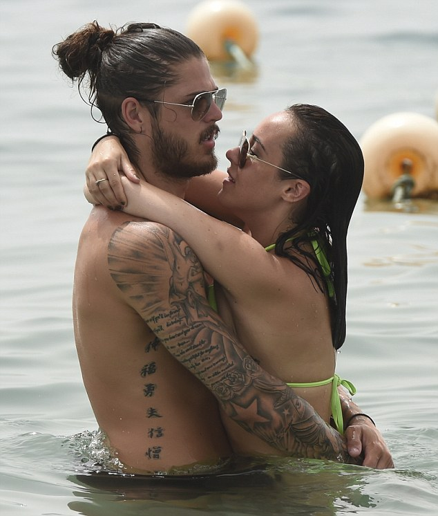 Still holding on: The pretty brunette clung to her boyfriend's neck as the played in the sea
