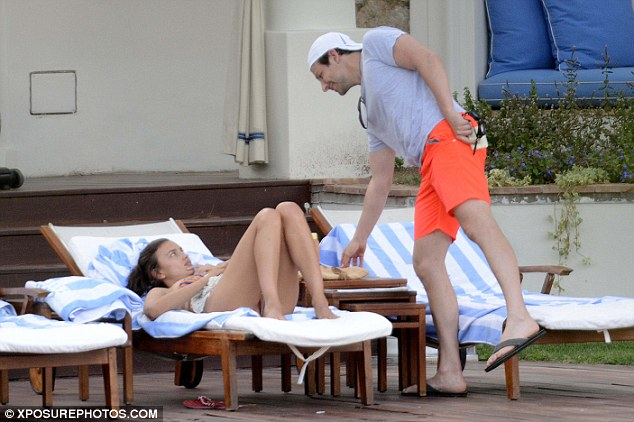 Beaming: Bradley offered his leggy girlfriend a cheeky grin as he picked up an object from an adjacent table
