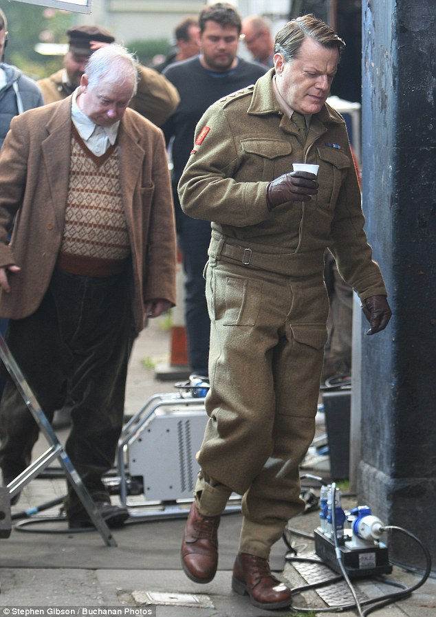 In character: The British star also rocked sturdy brown leather boots and slipped on matching gloves after revealing bright red nail polish on his hands