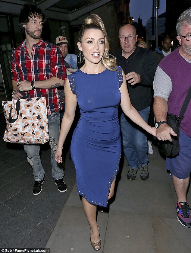 In good company: Dannii was joined by boyfriend Adrian Newman, who appeared to carry her colourful bag in his right hand