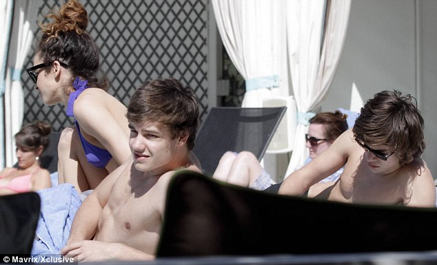 Pool side: Danielle Peazer, left, sits next to her topless One Direction boyfriend Liam Payne, middle and his band mate Harry Styles, right, in LA