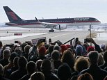 Supporters of U.S. Republican presidential candidate Donald Trump watch his plane arrive before a campaign rally in Dubuque, Iowa January 30, 2016. REUTERS/Rick Wilking