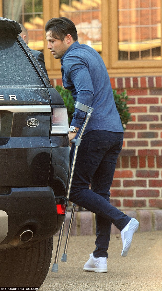 Hop to it: The TV presenter was seen hobbling out of the Essex home he shares with wife Michelle Keegan with the aid of crutches