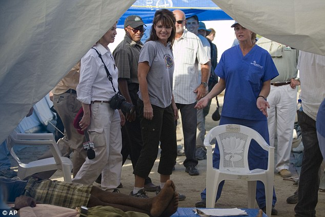 Speaking of the hopey, changey stuff... Mrs Palin peers into a tent in which cholera patients are fighting for their health