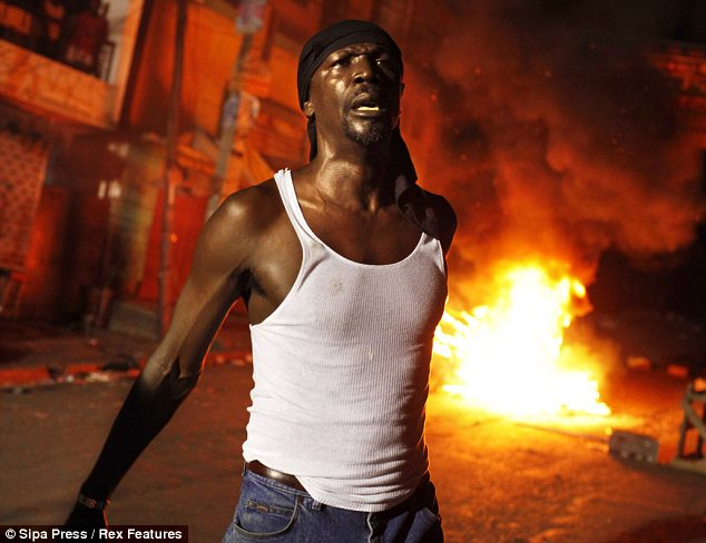 Anger: A protester is captured and behind him a fire erupts after a road blockage was set on fire