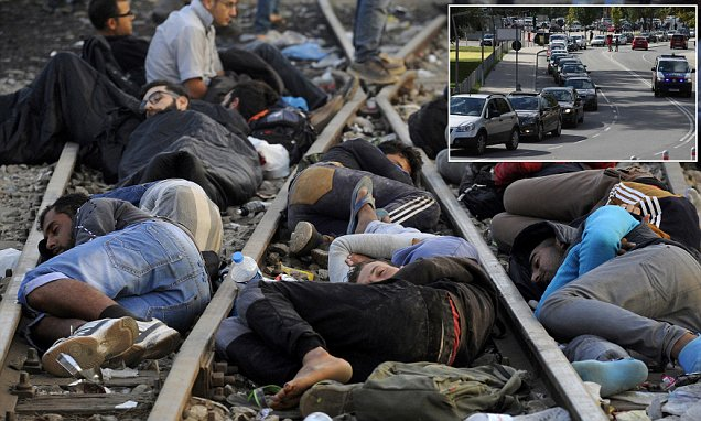Refugees sleep on railway tracks on journey to to Germany and Austria