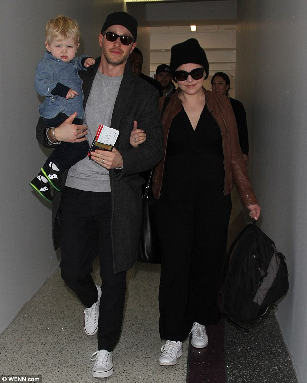 Low-key: Ginnifer Goodwin, 37, dressed down her baby bump as she departed LAX with her husband Josh Dallas, 34, and their 21-month-old son, Oliver, on Monday