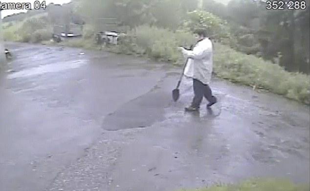 Murderers: Stuart Wareham leaves the scene of the burial having taken his jacket off