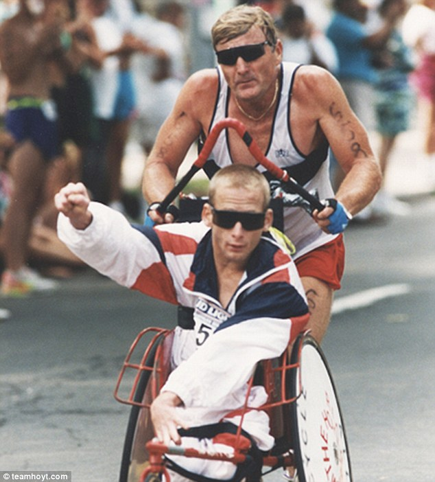 With his trademark right hand raised, Rick Hoyt travels over the finish line with his father Dick
