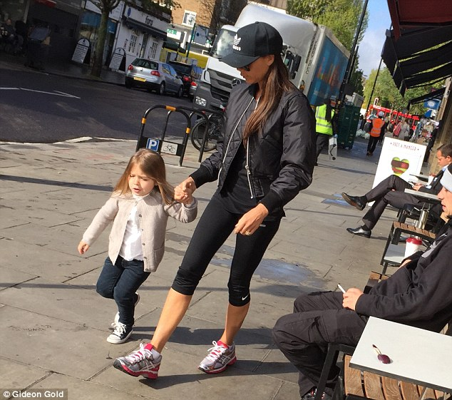 So close: Victoria Beckham and her three-year-old daughter Harper hold hands as they enjoy a day in the sunshine together in London on Wednesday, following their trip to Marrakech for David's birthday