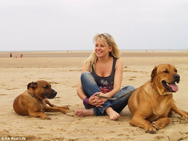 Hannah, originally from Surrey, poses on a beach with her two dogs. She now hopes to become a mother