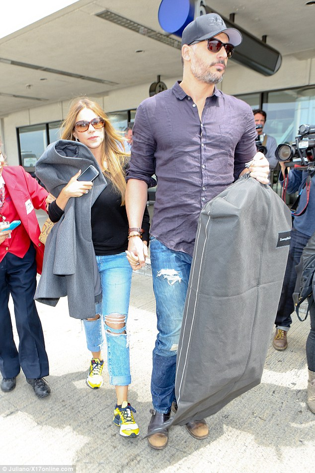 Casual for the occasion:The 42-year-old knockout was casual for her flight in ripped jeans, a black top and sneakers