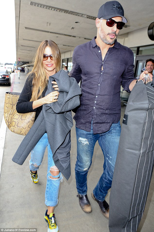 Leading the way!She concealed her eyes behind large sunglasses and carried a grey sweater with one as the other one was held by her hunky man Joe