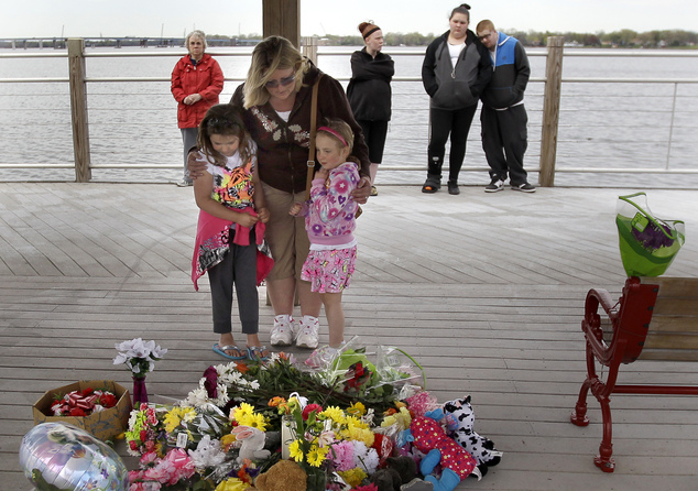 Heather, left, Christy and Caitlyn Betley  pause to pray after placing flowers at a memorial in the pavilion on the re-opened Trestle Trail near Fritse Park,...