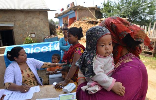 Nepalese residents bring their children to a UNICEF field clinic providing free vaccinations at Kot Danda in Lalitpur, Kathmandu Valley, on May 6, 2015