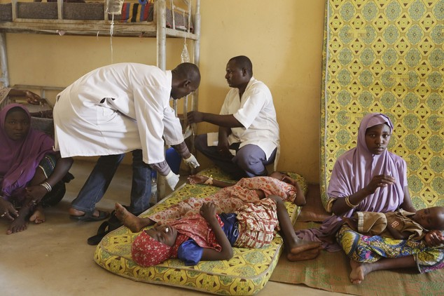 FILE - A Sunday, May 3, 2015 photo from files showing doctors as they attend to a sick child rescued by Nigerian soldiers from Boko Haram extremists at a ref...