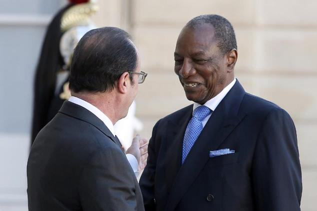 French President Francois Hollande (left) greets his Guinean counterpart Alpha Conde on April 22, 2015 in Paris