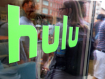 """FILE - This Saturday, June 27, 2015, file photo, shows the Hulu logo on a window at the Milk Studios space in New York, where a replica of the """"Seinfeld"""" set was on display. Some television companies are balking as more people watch shows online, and may start delaying the release of shows to streaming services like Netflix and Hulu. These studios fear that the success of streaming services might lead more households to cut back or drop cable TV services. It also comes as online services have been dabbling in creating their own television shows. (AP Photo/Dan Goodman, File)"""
