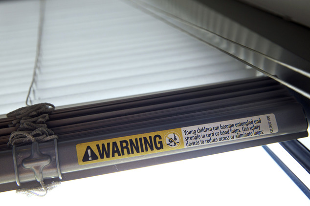 A label warns of strangulation risks from mini blind cords as seen on Wednesday, May 6, 2015, in Washington. The industry launched a campaign that encourages...
