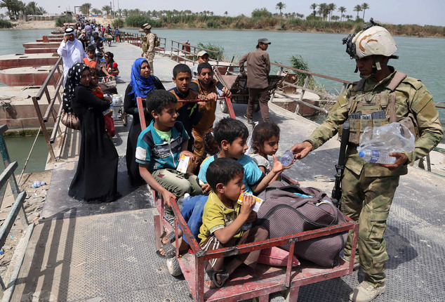 FILE - In this Saturday, April 18, 2015, file photo, Iraq security troops distribute bottles of water to displaced families from Ramadi on Bzebiz bridge 65 k...