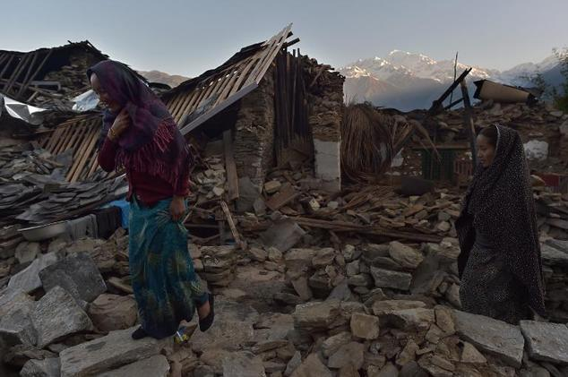 Villagers walk through the rubble of destroyed houses in the village of Barpak in north central Nepal, May 4, 2015
