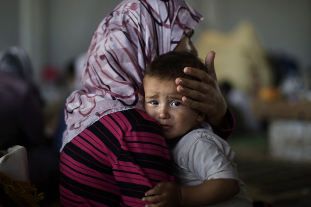 FILE - In this Wednesday, Sept. 5, 2012 file photo, Amjad Al-Saleh, whose family fled their home in Marea due to Syrian government shelling, is comforted by ...