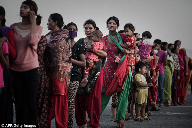 Women queue for food at a shelter in Kathmandu nine days after the earthquake struck. Aid workers warn that thousands of women and girls are at risk of being snatched by sex traffickers amid the devastation