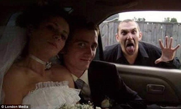 When the couple leaned in for this intimate pose, they had no idea someone else in the background wanted to share in their special day... by pulling a stupid face at the window of their bridal car